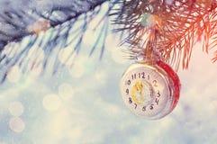 Neues Jahr-Hintergrund-neues Jahr-Glasweihnachtsspielzeug in der Form der Uhr den Sylvesterabend, auf schneebedecktem Tannenbauma Stockfoto