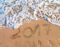 Neues Jahr 2017 ist das kommende Konzept, das auf sandigen Strand geschrieben wird Stockfotografie