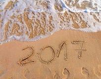 Neues Jahr 2017 ist das kommende Konzept, das auf sandigen Strand geschrieben wird Stockfotos