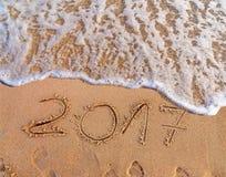 Neues Jahr 2017 ist das kommende Konzept, das auf sandigen Strand geschrieben wird Lizenzfreie Stockbilder