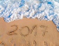 Neues Jahr 2017 ist das kommende Konzept, das auf sandigen Strand geschrieben wird Lizenzfreies Stockfoto