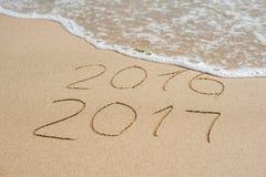 Neues Jahr 2017 ist kommendes Konzept - Aufschrift 2016 und 2017 auf einem Strandsand, die Welle umfasst fast die Stellen 2016 Lizenzfreie Stockfotografie