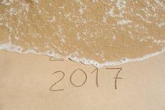Neues Jahr 2017 ist kommendes Konzept - Aufschrift 2016 und 2017 auf einem Strandsand, die Welle umfasst fast die Stellen 2016 Stockbild