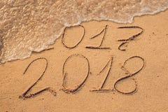 Neues Jahr 2018 ist kommendes Konzept - Aufschrift 2017 und 2018 auf einem Strandsand, die Welle umfasst fast die Stellen 2017 Lizenzfreie Stockfotografie