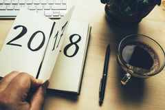 Neues Jahr 2018 ist kommendes Konzept Hand schlägt Notizblockblatt auf Holztisch leicht 2017 dreht sich, 2018 sich öffnet Stockbild