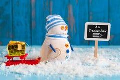Neues Jahr ist kommendes Konzept Schneemann mit rotem Schlitten Stockfotografie