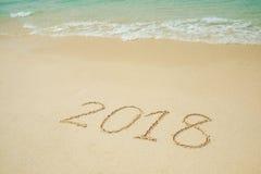 Neues Jahr 2018 kommt 2018 auf einem Strandsand, die Welle Stockfoto