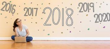2018 neues Jahr mit der jungen Frau, die einen Laptop verwendet Lizenzfreie Stockbilder