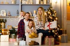 Neues Jahr ` s Bild der glücklichen Familie auf Hintergrund von Weihnachtsdekorationen, Kiefer Lizenzfreie Stockfotos