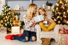 Neues Jahr ` s Bild der Mutter Geschenk gebend der Tochter, die auf Stuhl sitzt Lizenzfreie Stockbilder