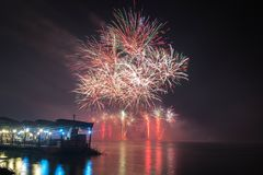 Neues Jahr ` s Eve Fireworks startete vom Wasser mit Reflexionen Stockbild