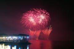 Neues Jahr ` s Eve Fireworks startete vom Wasser mit Reflexionen Stockfotografie