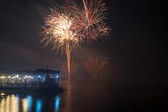 Neues Jahr ` s Eve Fireworks startete vom Wasser mit Reflexionen lizenzfreies stockfoto