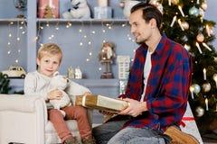 Neues Jahr ` s Foto des Sohns und des Vatis mit Geschenk Lizenzfreie Stockbilder