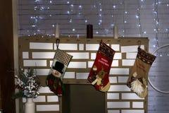 Neues Jahr ` s Innenraum mit einem Kamin, einem Lehnsessel und LED-Girlanden Stockbilder