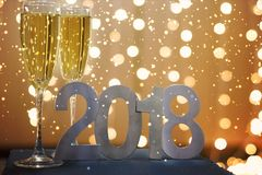 Neues Jahr ` s Karte im Jahre 2018 mit Champagner auf dem Hintergrund von festlichen Girlanden, Flocken des weißen Schnees Lizenzfreie Stockfotografie