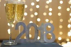 Neues Jahr ` s Karte im Jahre 2018 mit zwei Gläsern Champagner auf dem Hintergrund von festlichen Girlanden Stockfoto