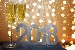 Neues Jahr ` s Karte von 2018 mit Champagner auf dem Hintergrund von festlichen brennenden Girlanden Lizenzfreie Stockfotografie