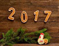 Neues Jahr `s Konzept Abbildung 2017 und Hahn vom Lebkuchen, Tannenzweig auf einem hölzernen Hintergrund Lizenzfreie Stockbilder