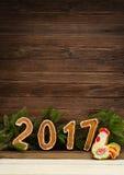 Neues Jahr `s Konzept Abbildung 2017 und Hahn vom Lebkuchen, Tannenzweig auf einem hölzernen Hintergrund, Raum für Text Lizenzfreie Stockbilder