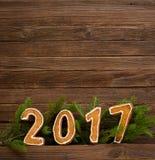 Neues Jahr `s Konzept Abbildung 2017 vom Lebkuchen, Tannenzweig auf einem hölzernen Hintergrund Stockfotografie