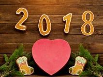 Neues Jahr `s Konzept Packen Sie Herz geformte Lebkuchenplätzchen, Tannenzweig und die Nr. 2018 auf dem hölzernen Hintergrund ein Lizenzfreies Stockbild