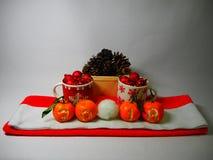 Neues Jahr ` s Mandarinen mit der Aufschrift 2018 auf dem Hintergrund eines Korbes mit Kegeln und Becher mit gemalten Schneeflock Lizenzfreies Stockbild