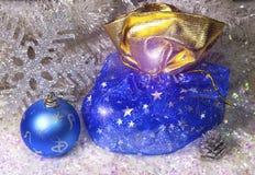 Neues Jahr ` s Sack mit Geschenken und ein Ball auf einem Schneehintergrund Lizenzfreie Stockfotos