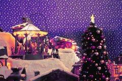 Neues Jahr ` s Stadt in der Miniatur mit Karussell für Kinder, Weihnachtsbaum, Schneestraßen Feldfarben: violett, purpurrot, weiß Lizenzfreies Stockbild