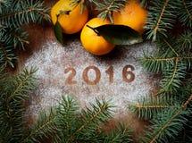 Neues Jahr 2016, Tangerineniederlassungen und Nadeln auf einem hölzernen Hintergrund Lizenzfreies Stockfoto