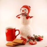 Neues Jahr-Tee mit Plätzchen, Kerzen und gestricktem Schneemann Lizenzfreies Stockbild