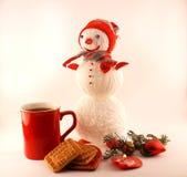 Neues Jahr-Tee mit Plätzchen, Kerzen und gestricktem Schneemann Stockfoto