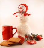 Neues Jahr-Tee mit Plätzchen, Kerzen und gestricktem Schneemann Stockfotografie