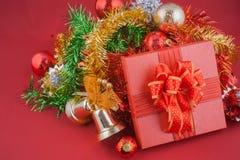 Neues Jahr und Weihnachtsgeschenkbox mit Dekorationen auf rotem Hintergrund Stockfotografie