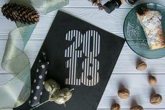 Neues Jahr und Winter eingestellt auf weißen hölzernen Hintergrund mit den Schwarzen und natürlichen und Golddetails, gestreiftem Lizenzfreie Stockfotografie