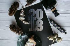 Neues Jahr und Winter eingestellt auf weißen hölzernen Hintergrund mit den Schwarzen und natürlichen und Golddetails, gestreiftem Stockfotografie