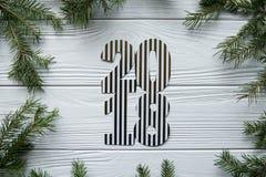 Neues Jahr und Winter eingestellt auf weißen hölzernen Hintergrund mit Tannenbaum, gestreiftem goldenem und weißem 2018 Stockbild