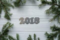 Neues Jahr und Winter eingestellt auf weißen hölzernen Hintergrund mit Tannenbaum, gestreiftem goldenem und weißem 2018 Lizenzfreies Stockbild