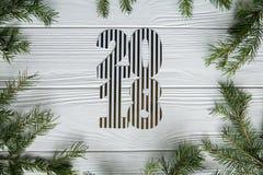 Neues Jahr und Winter eingestellt auf weißen hölzernen Hintergrund mit Tannenbaum, gestreiftem goldenem und weißem 2018 Stockfoto