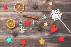 Neues Jahr-Weihnachtsmotiv mit dekorativen 2018 Zahlen, Anissternen, Zimtstangen, dekorativen Sternen und Schneeflocke auf hölzer Lizenzfreie Stockbilder