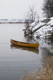 Neues Kanu, das auf das ruhige Wasser im Wintersonnenuntergang schwimmt Lizenzfreie Stockfotos