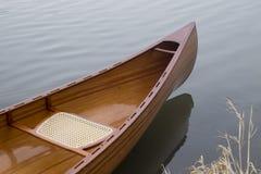 Neues Kanu, das auf das ruhige Wasser im Wintersonnenuntergang schwimmt Lizenzfreie Stockfotografie