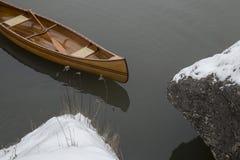 Neues Kanu, das auf das ruhige Wasser im Wintersonnenuntergang schwimmt Stockfoto