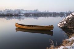 Neues Kanu, das auf das ruhige Wasser im Wintersonnenuntergang schwimmt Lizenzfreies Stockbild