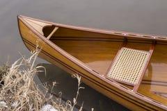 Neues Kanu, das auf das ruhige Wasser im Wintersonnenuntergang schwimmt Stockbild