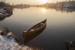 Neues Kanu, das auf das ruhige Wasser im Wintersonnenuntergang schwimmt Lizenzfreies Stockfoto