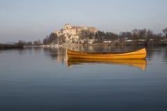 Neues Kanu, das auf das ruhige Wasser im Wintersonnenuntergang schwimmt Stockbilder
