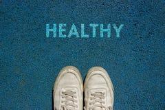 Neues Lebenkonzept, Sportschuhe und das Wort GESUND! geschrieben auf blauen Gehwegboden, Motivslogan lizenzfreies stockbild