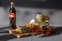 Neues Menü der Fotosession des Kaffeehauses, der frischen Sandwich-, Glasflasche Coca Cola, der Pommes-Frites und des Ketschups a stockfoto