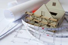 Neues Musterhaus auf Architekturplanplan am Schreibtisch Lizenzfreie Stockfotos